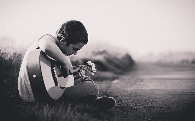 A boy playing the guitar delicately