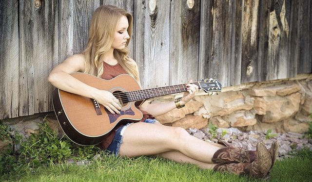 A girl sitting on grass and playing a guitar