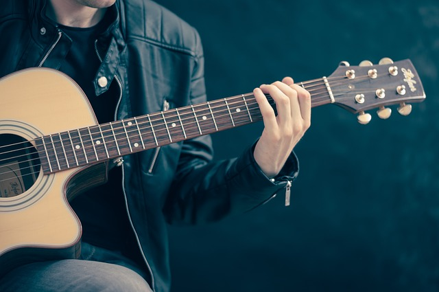 5 best tips to practice guitar - A man playing a guitar freely