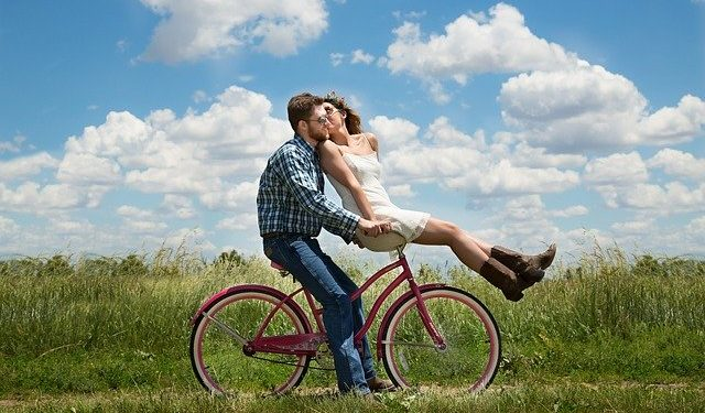 Young couple riding a bicycle while kissing