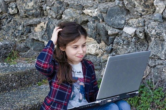 A small girl having an issue with her lap top - 5 things to talk about with your children every day
