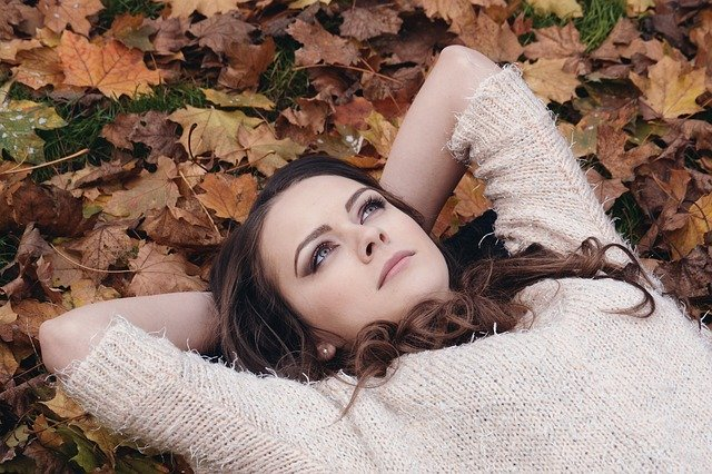 A young girl lying on a ground with lot of leaves and thinking looking at sky