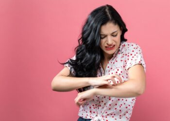 Young woman scratching her itchy arm. Skin problem.